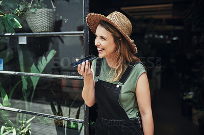 Buy stock photo Cropped shot of an attractive young business owner standing and sending voice notes on her cellphone at the floristry entrance