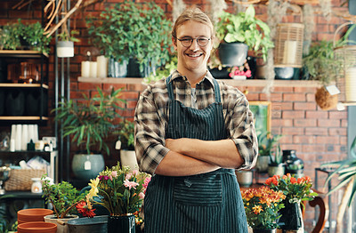 Buy stock photo Cropped portrait of a handsome young business owner standing in his floristry alone with his arms folded