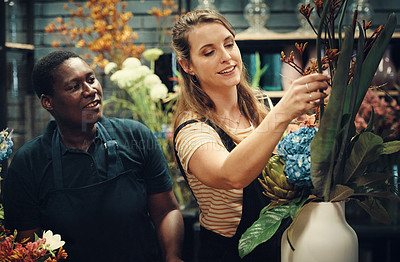 Buy stock photo Cropped shot of two attractive young florists standing together and adjusting the flower arrangements in her shop