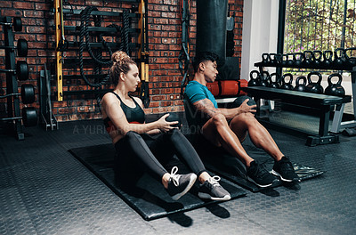 Buy stock photo Cropped shot of two young sportspeople working out with medicine balls in a gym
