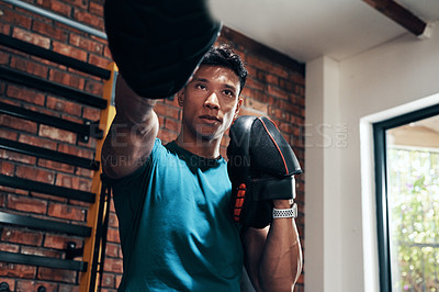 Buy stock photo Cropped shot of a handsome young male boxer working out in a gym