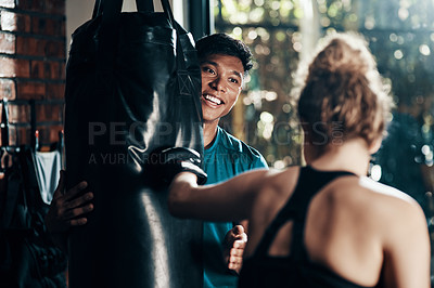 Buy stock photo Cropped shot of a handsome young male fitness instructor coaching a female boxer in a gym
