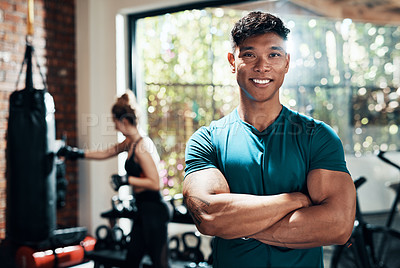 Buy stock photo Cropped shot of a handsome young sportsman standing with his arms crossed in a gym with his fitness partner in the background
