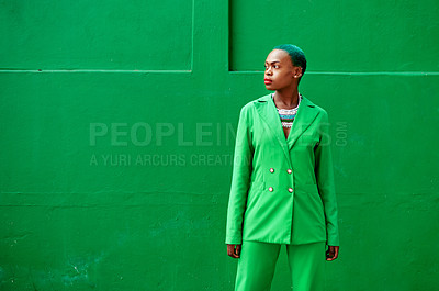Buy stock photo Cropped shot of an attractive young woman posing while standing against a green background outside during the day
