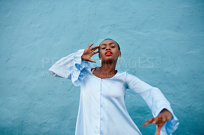 Buy stock photo Portrait of an attractive young woman posing while standing against a blue background outside during the day