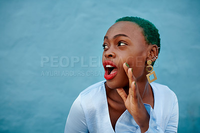 Buy stock photo Cropped shot of a cheerful young woman posing while standing against a blue background outside during the day