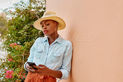 Buy stock photo Cropped shot of an attractive young woman texting on her cellphone while leaning on a wall outside during the day