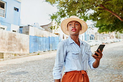 Buy stock photo Cropped shot of an attractive young woman texting on her cellphone while walking in a street outside during the day