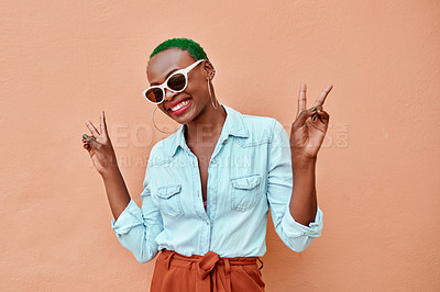 Buy stock photo Portrait of a cheerful young woman posing while showing the peace sign against a orange background