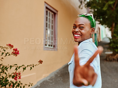 Buy stock photo Portrait of a cheerful young woman looking back at the camera while showing the peace sign outside during the day
