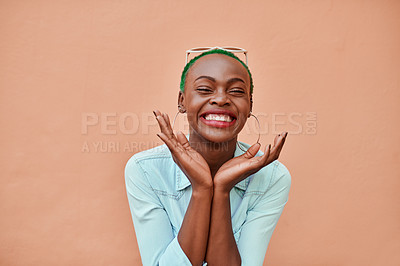 Buy stock photo Portrait of a cheerful young woman posing while standing against a orange background outside during the day