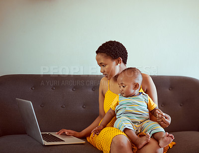 Buy stock photo Shot of a young woman using a laptop while relaxing on the sofa with her baby boy
