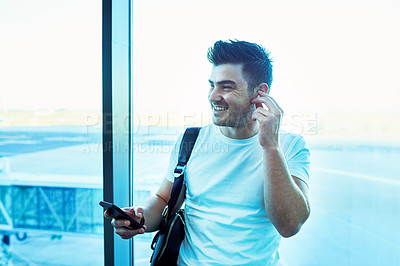 Buy stock photo Shot of a young man using a smartphone and earphones at an airport