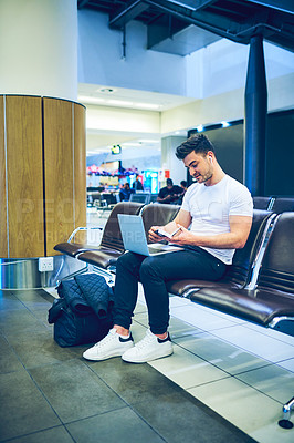Buy stock photo Shot of a young man using a laptop and getting his passport ready before his flight at an airport