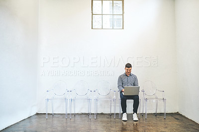 Buy stock photo Shot of a young man using a laptop while sitting on a chair against a white wall