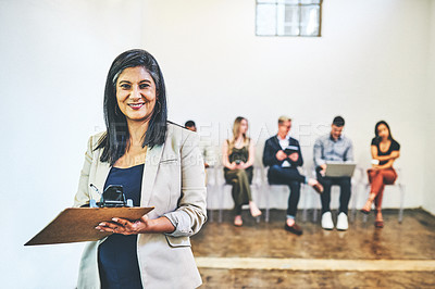 Buy stock photo Portrait of a mature businesswoman holding a clipboard while standing in front of candidates who are waiting in line