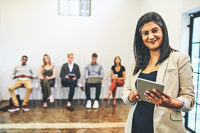 Buy stock photo Portrait of a mature businesswoman using a digital tablet while standing in front of candidates who are waiting in line