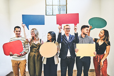 Buy stock photo Shot of a group of businesspeople holding colourful speech bubbles in an office