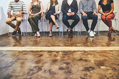 Buy stock photo Closeup shot of a group of unrecognisable businesspeople sitting together on chairs against a white wall