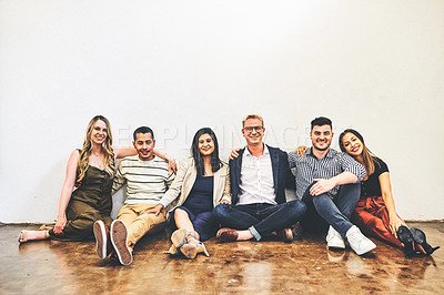 Buy stock photo Portrait of a group of businesspeople sitting on the floor against a white wall