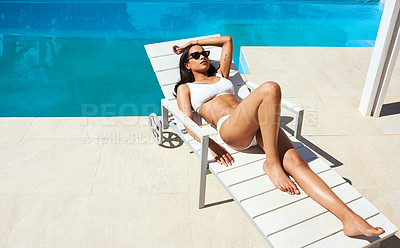 Buy stock photo Shot of a beautiful young woman relaxing on a lounger by the poolside