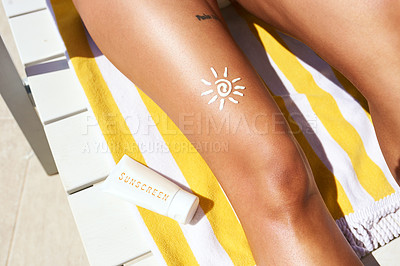 Buy stock photo Cropped shot of an unrecognizable woman wearing sunscreen while relaxing outside on a lounger
