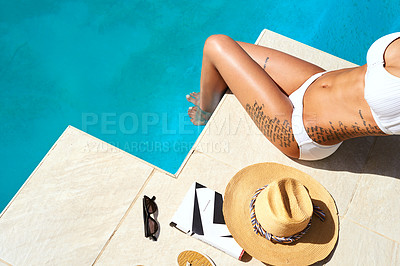 Buy stock photo Shot of an unrecognizable woman relaxing by the pool