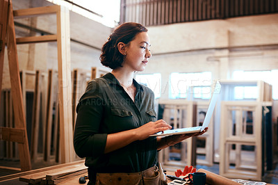 Buy stock photo Shot of a female carpenter using a laptop in her workshop