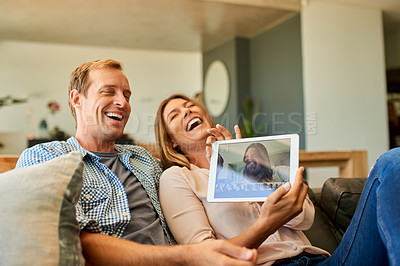 Buy stock photo Shot of a happy young couple using a digital tablet to take distorted pictures of themselves at home