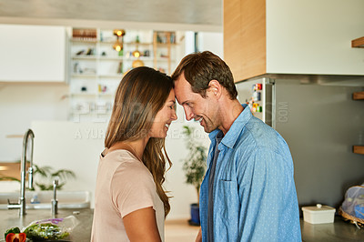 Buy stock photo Cropped shot of an affectionate young couple standing in the kitchen together and sharing an intimate moment