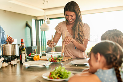 Buy stock photo Cropped shot of an attractive young woman serving a greek salad for her family during lunch at home