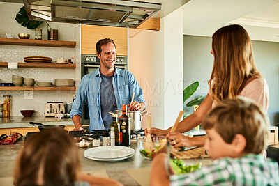 Buy stock photo Cropped shot of a handsome young man cooking lunch for his family during a day off at home