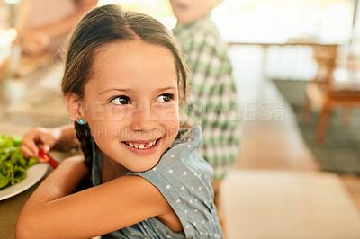 Buy stock photo Cropped shot of a happy young girl sitting at the table and about to eat lunch with her family