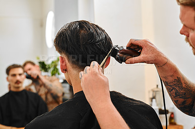 Buy stock photo Cropped shot of a handsome young barber sitting and shaving a client's hair in his salon