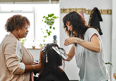 Buy stock photo Cropped shot of two attractive young hairdressers standing and applying hair dye to their client's hair in a salon