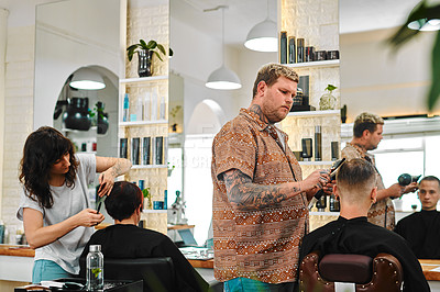 Buy stock photo Cropped shot of two young hairdressers standing together and cutting their client's hair in a salon