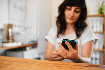 Buy stock photo Cropped shot of an attractive young hairdresser standing behind the reception desk and using a credit card machine