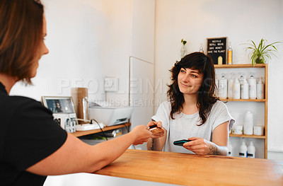 Buy stock photo Cropped shot of an attractive young hairdresser standing behind a desk and accepting a client's credit card for a payment