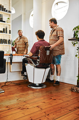 Buy stock photo Full length shot of a handsome young barber standing next to his client and having a discussion in the salon