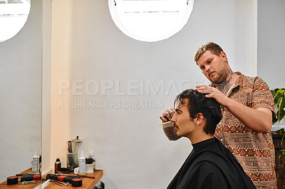 Buy stock photo Cropped shot of a handsome young barber standing in the salon and styling his client's hair