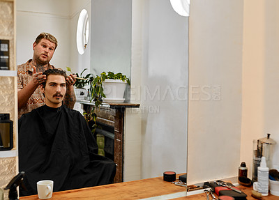 Buy stock photo Cropped shot of a handsome young barber standing next to his client and having a discussion in the salon