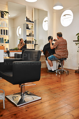 Buy stock photo Full length shot of a handsome young barber sitting and shaving a client's hair in his salon