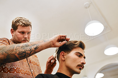 Buy stock photo Cropped shot of a handsome young barber standing and cutting a client's hair in his salon