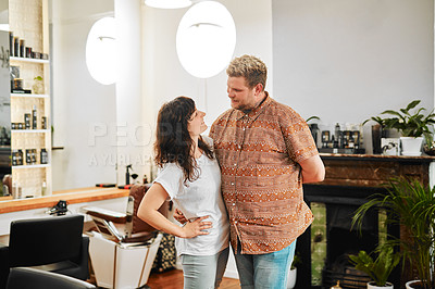 Buy stock photo Cropped shot of a happy young couple standing arm in arm together in their salon