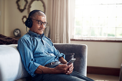 Buy stock photo Shot of a senior man using a smartphone and headphones while relaxing at home