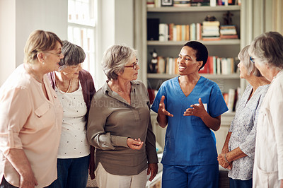 Buy stock photo Cropped shot of an attractive young nurse standing with her senior patients in the living room of a nursing home