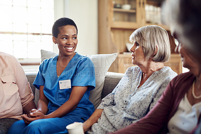 Buy stock photo Cropped shot of an attractive young nurse sitting with her senior patients in the living room of a nursing home