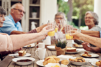 Buy stock photo Cropped shot of a group of seniors sitting together and raising their fruit juice glasses for a toast