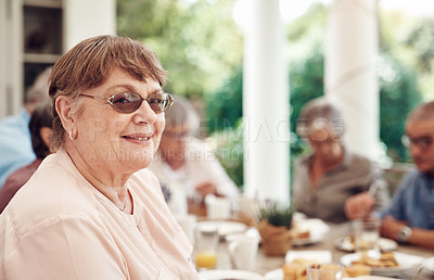 Buy stock photo Cropped portrait of a happy senior woman sitting and enjoying a tea party with her friends outdoors