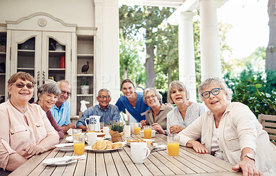 Buy stock photo Cropped portrait of a group of senior citizens sitting together and enjoying a tea party outdoors